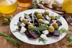 Salade de betterave (betterave) avec du fromage, les olives et l'arugula du plat blanc Photo libre de droits
