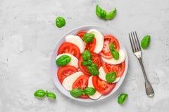 Salade de Caprese avec les tomates et le fromage mûr de mozzarella, les feuilles fraîches de basilic et la fourchette sur le fond photographie stock