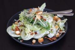 Salade de Cesar dans le plat noir photo stock