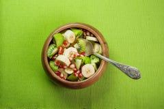 Salade de fruits avec la banane, le kiwi et la grenade dans une cuvette en bois a Images libres de droits
