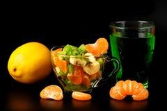 Salade de fruits, citron, segments de mandarine et verre avec la boisson Photographie stock