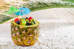 Salade de fruits frais en ananas avec des parapluies de cocktail sur la plage Image libre de droits