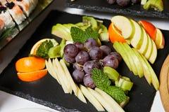 Salade de fruits pour des vegans, des morceaux d'ananas, des oranges et le kiwi d'un plat noir photos libres de droits
