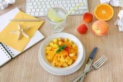 Salade de fruits saine de casse-croûte de pêche, abricot, orange dans le lieu de travail Image stock