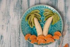 Salade de fruits saine pour des enfants de kiwi, de bananes et de mandarines image libre de droits