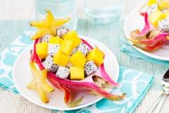 Salade de fruits tropicale dans le pitahaya, mangue, bols de fruit du dragon avec un verre de jus Photographie stock