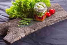 Salade de légume frais avec des herbes sur un conseil en bois, fond texturisé noir Avec l'espace pour le texte Nourriture saine photographie stock libre de droits