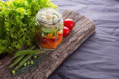 Salade de légume frais avec des herbes sur un conseil en bois photographie stock