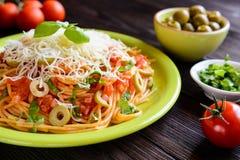 Salade de pâtes de spaghetti avec la sauce tomate, les olives, le gouda et le basilic Image libre de droits