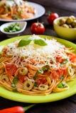 Salade de pâtes de spaghetti avec la sauce tomate, les olives, le gouda et le basilic Photographie stock