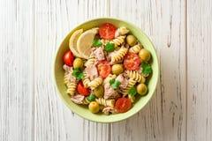 Salade de pâtes de Fusilli avec le thon, les tomates, les olives et le persil sur le fond en bois blanc Images stock
