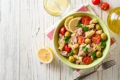 Salade de pâtes de Fusilli avec le thon, les tomates, les olives et le persil sur le fond en bois blanc Photo stock