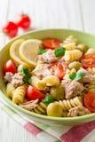 Salade de pâtes de Fusilli avec le thon, les tomates, les olives et le persil sur le fond en bois blanc Photographie stock libre de droits