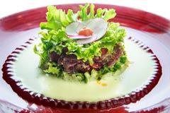 Salade de plan rapproché avec l'écrimage de viande et de fleur fait à partir du radis sur le plat rouge Photos libres de droits