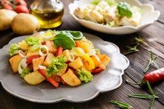 Salade de pomme de terre frite avec de la laitue, le poivre, l'oignon et les poissons cuits au four fi Photographie stock libre de droits