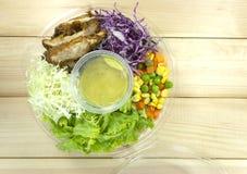 Salade de poulet dans la boîte en plastique sur le plancher en bois photographie stock libre de droits