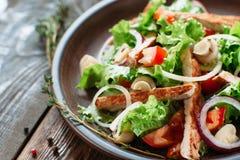 Salade de poulet dans le plat d'argile sur l'espace libre en bois Image stock