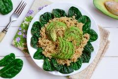 Salade de quinoa, d'avocat et d'épinards à un plat blanc et à un arrière-plan en bois blanc Recette de quinoa d'avocat de Vegan V Photo stock