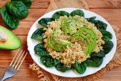 Salade de quinoa d'avocat Salade facile de quinoa avec les feuilles d'épinards et les tranches d'avocat fraîches d'un plat servi  Photo libre de droits