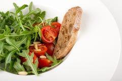 Salade de Rocket avec des tomates-cerises et des pignons Photos stock