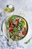 Salade de thon avec des tomates-cerises, des feuilles d'arugula et l'oignon rouge dessus photographie stock libre de droits