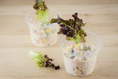 Salade de thon dans la tasse sur la table en bois Images stock