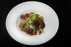 Salade de veau, salade avec de grandes tranches de veau et légumes frais d'un plat sur un fond noir image libre de droits
