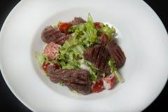 Salade de veau, salade avec de grandes tranches de veau et légumes frais d'un plat sur un fond noir photos libres de droits
