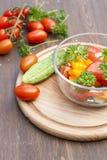 Salade des tomates fraîches et du concombre jaunes et roses avec le persil dans un bol en verre Image libre de droits