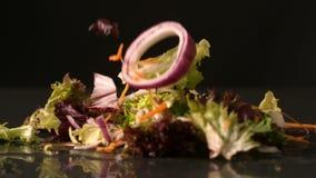 Salade die op zwarte oppervlakte vallen stock footage