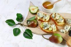 Salade et bruschette douces fraîches de poires avec du fromage bleu, noix sur le fond de conseil en bois Fin vers le haut Configu photographie stock