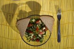 Salade et pain sur un tapis en bambou jaune sur le fond en bois photo stock