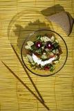 Salade et pain sur un tapis en bambou jaune sur le fond en bois photographie stock libre de droits