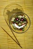 Salade et pain sur un tapis en bambou jaune sur le fond en bois photos stock