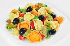 Salade faite avec le tortellini, olives, brocoli, poivron rouge, sur un plat images libres de droits
