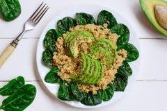 Salade faite maison de quinoa, d'avocat et d'épinards à un plat blanc et à un arrière-plan en bois blanc Recette végétarienne de  Photographie stock