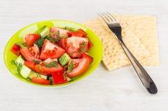 Salade, fourchette et pain croustillant végétaux sur la table Photos libres de droits