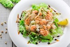Salade fraîche avec la crevette, les saumons, le calmar, l'avocat et les écrous sur le petit morceau photos stock