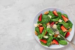 Salade fraîche avec la fraise, les feuilles d'épinards, le parmesan et les noix nourriture saine de régime de cétonique Vue supér photo libre de droits