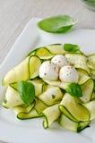Salade fraîche de courgette avec le basilic et mozzarella d'un plat Images stock
