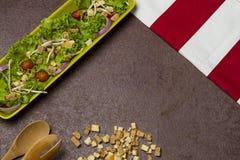 Salade fraîche de laitue et d'oignon de tomate avec le tissu rayé rouge, les dentelles de pain et la cuillère en bois image stock