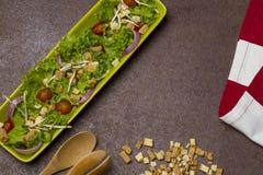 Salade fraîche de laitue et d'oignon de tomate avec le tissu rayé rouge, les dentelles de pain et la cuillère en bois images stock