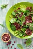 Salade fraîche de ressort avec l'arugula, les feuilles de betterave, l'avocat, les tranches oranges rouges et la canneberge Photographie stock