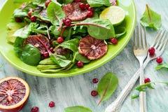 Salade fraîche de ressort avec l'arugula, les feuilles de betterave, l'avocat, les tranches oranges rouges et la canneberge Photo libre de droits