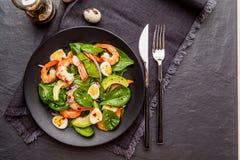 Salade fraîche et saine avec des crevettes, épinards et avocat sur un blac images libres de droits