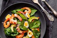 Salade fraîche et saine avec des crevettes, épinards et avocat sur un blac photographie stock libre de droits