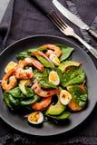 Salade fraîche et saine avec des crevettes, épinards et avocat sur un blac photographie stock