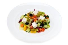 Salade grecque dans un plat blanc sur un fond blanc Photo stock