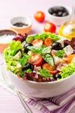 Salade grecque fraîche avec les légumes, le feta et les olives noires dans la cuvette blanche sur le fond en bois pourpre photo stock