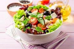 Salade grecque fraîche avec les légumes, le feta et les olives noires dans la cuvette blanche sur le fond en bois pourpre image stock